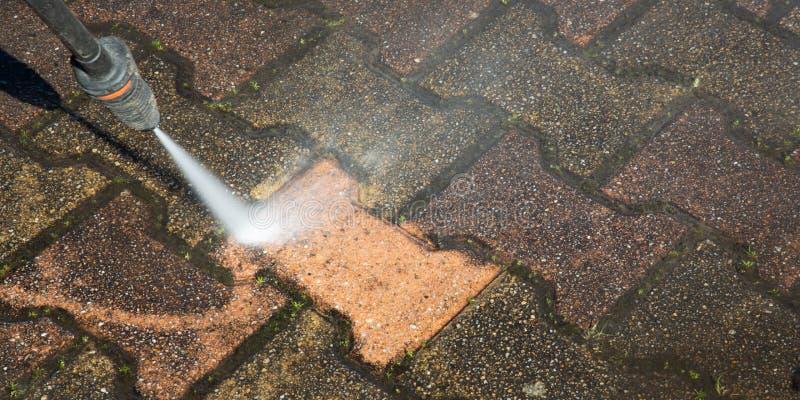 Bodenreinigung im Freien mit einem Druck Wasserstrahl in der Fahnenpanorama-Netzschablone lizenzfreies stockbild