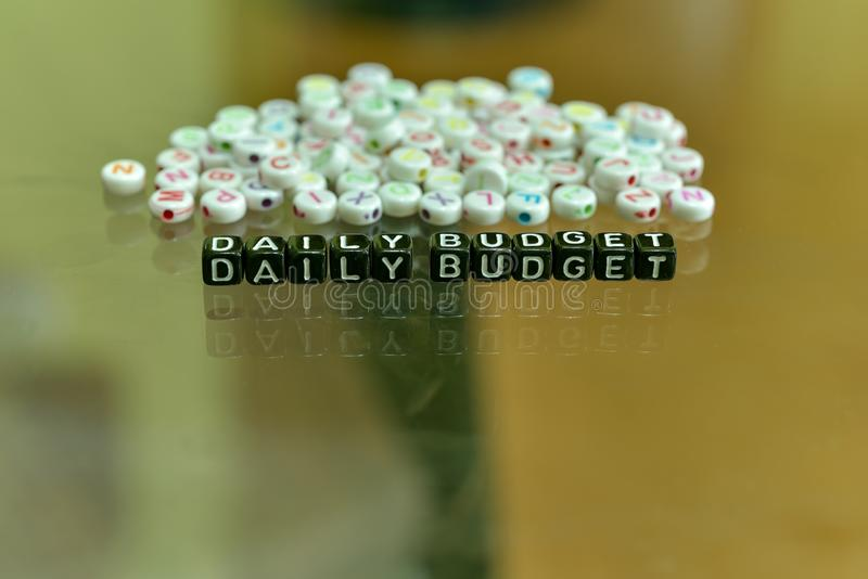 DAILY BODGET  written with Acrylic Black cube with white Alphabet Beads on the Glass Background.  stock photo
