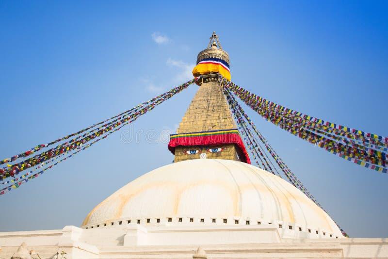 Bodhnath Stupa med buddha ögon och bönflaggor, blå himmel för frikänd, Katmandu arkivfoto