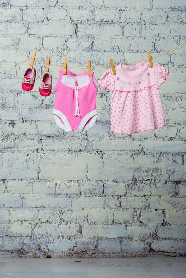 Bodic ` s детей розовые, платье и красные ботинки для девушки, сушат на веревочке против белой кирпичной стены стоковое фото rf