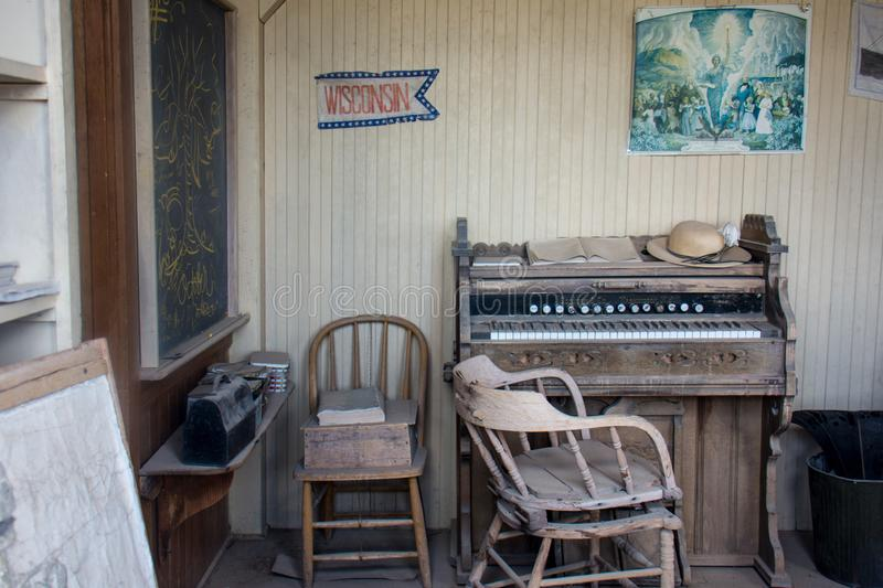 Bodie, California - Interior of the old school house, with a piano, chairs, blackboard and posters in a state of. Interior of the old school house, with a piano stock photos
