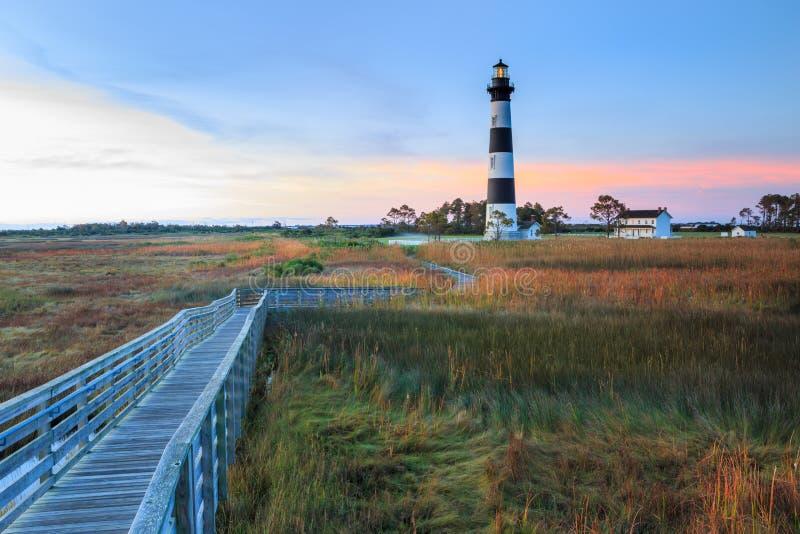 Bodie Island Lighthouse Boardwalk Marsh North Carolina. Wooden pedestrian boardwalk winds through marsh grasses toward Bodie Island Lighthouse at daybreak in stock photos