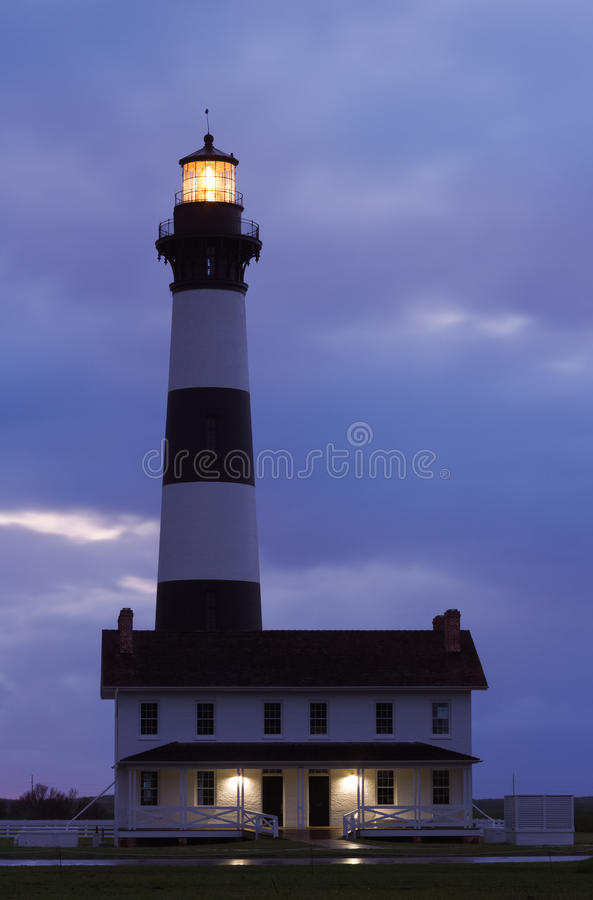 Bodie Island LIghthouse Before Sunrise. The light of the yet-risen sun lights the clouds with color behind the Bodie Island Lighthouse and keeper's dwelling in royalty free stock images