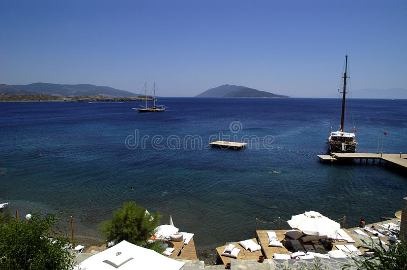 Bodrum, Turkey. Coast at Bodrum, Turkey, mountains in distance, boats, pier, blue water royalty free stock image