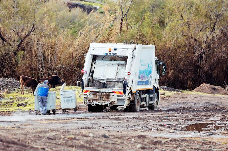 Garbage collector truck and worker collecting the garbage cans in a rural meadow field. Bodrum, Turkey-January, 2019: Garbage collector truck and worker stock photo