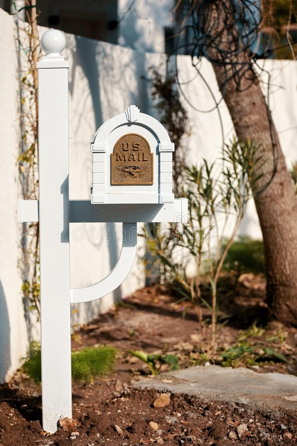 White wooden US mail letterbox with metal emboss eagle symbol on the front yard of a house. Editorial stock photo