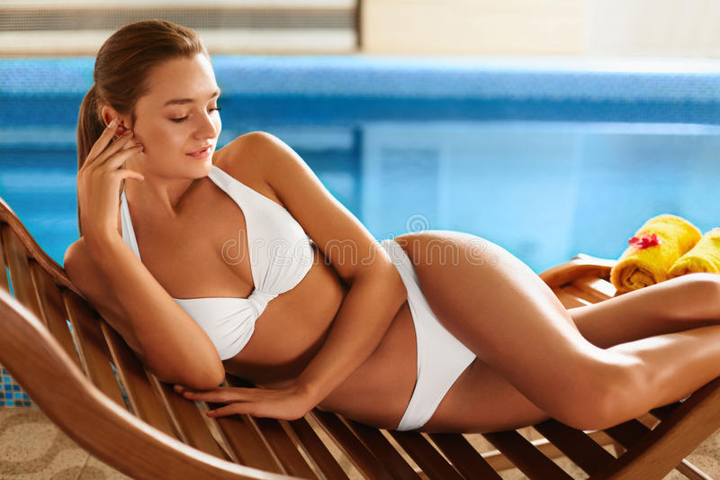 Body Ð¡are. Woman Relaxing at the Pool. Spa. Body Care. Attractive Healthy Young Caucasian Woman With Perfect Tanned Slim Body And Dark Beautiful Hair In White stock image