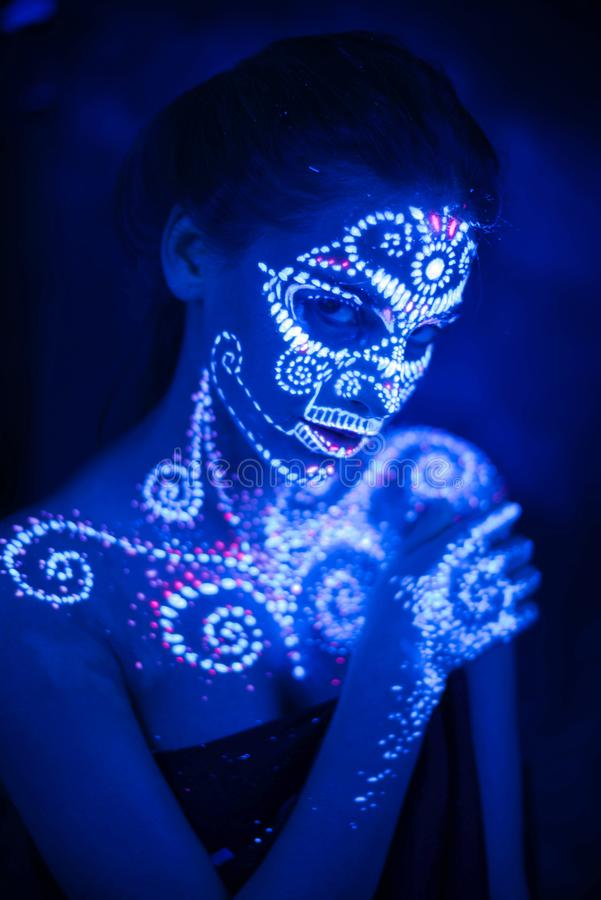 Body art on the body and hand of a girl glowing in the ultraviolet light stock photography