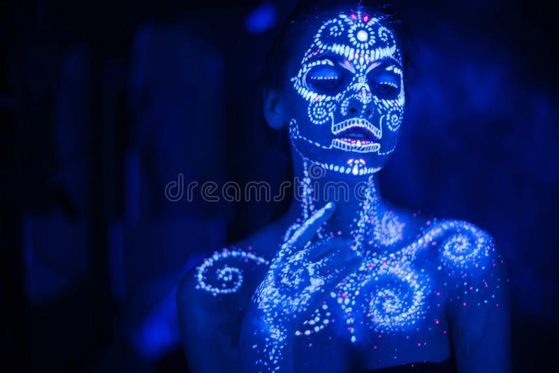 Body art on the body and hand of a girl glowing in the ultraviolet light stock photos
