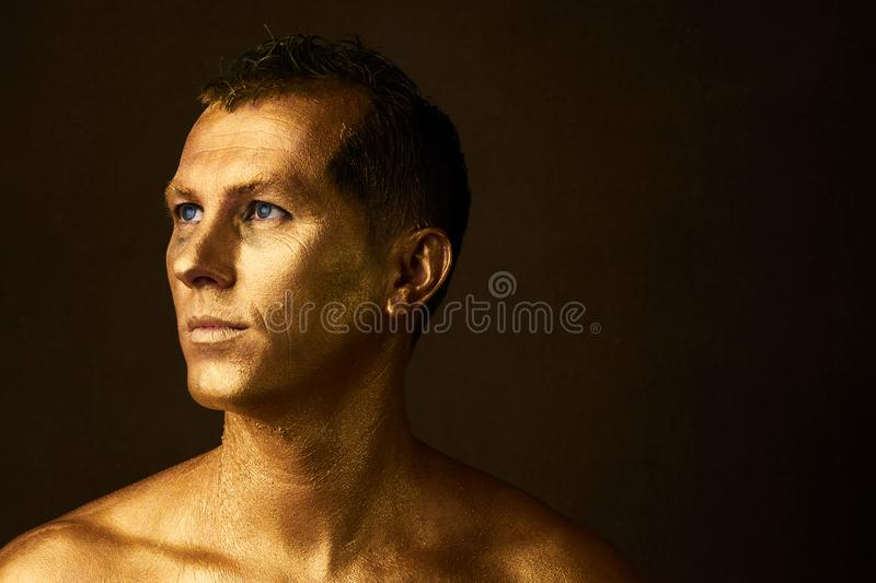 Body art paint with gold on face of man over dark background royalty free stock images