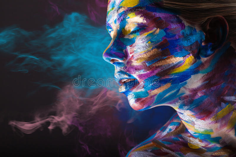 Body art. Young woman with colorful make-up and body art on a black background with multi-colored smoke