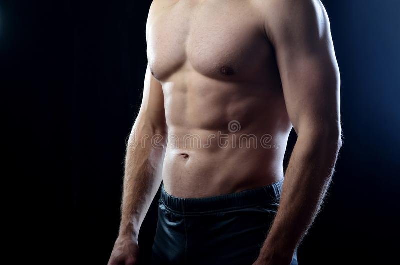 Athletic man with strained balanced chest and abdominal muscles on a dark studio background stock photography
