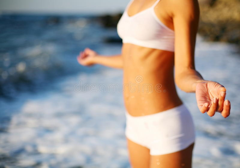 Body of a beautiful girl on the beach. Body of a beautiful girl in a meditation on the beach stock image