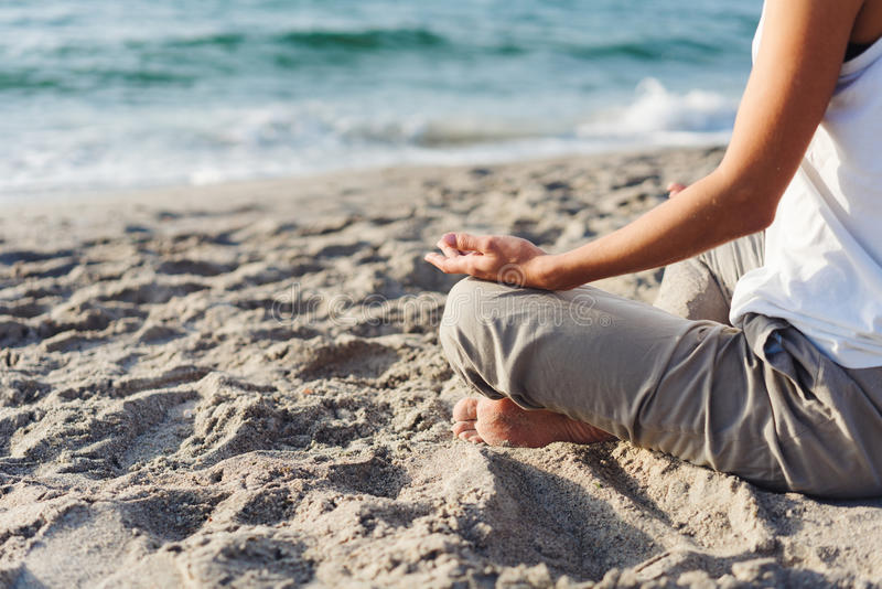 Body of a beautiful girl in a meditation. On the beach royalty free stock photos