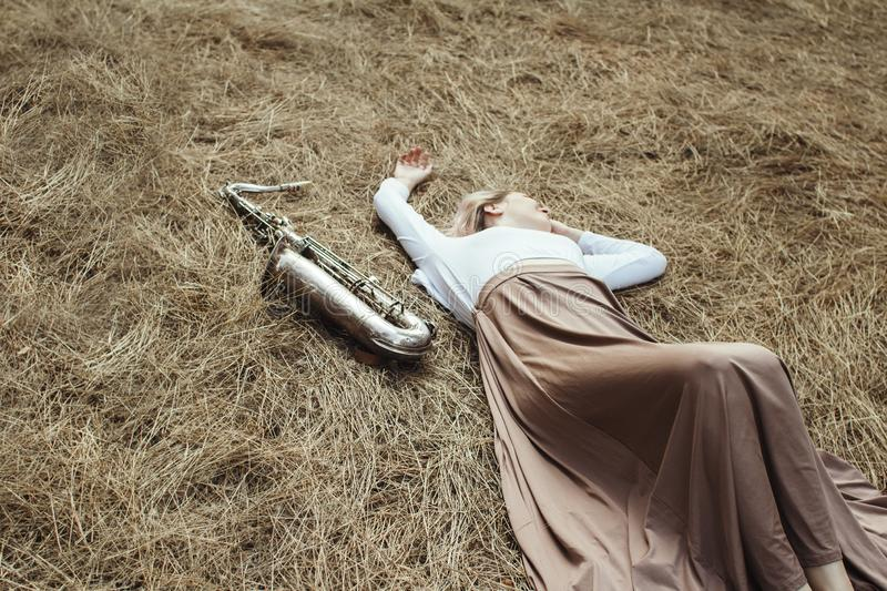 Body of a beautiful young woman in long dress lying on the dry grass next to the saxophone, girl in the summer on the hay rests royalty free stock photography