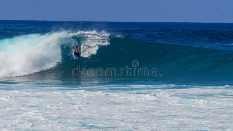 A body boarder rides a large wave and performs at pipeline stock photo