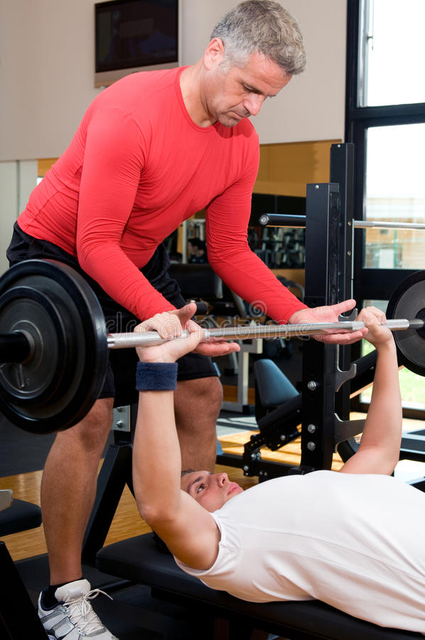 Body buidling exercise at gym. Young man doing weigths on a bench press with the help of the mature instructor at gym stock image