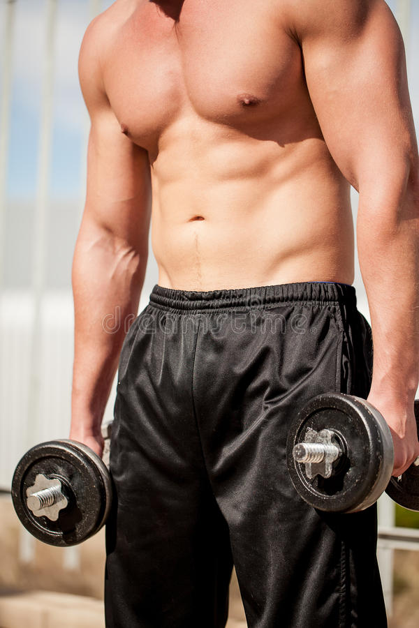 Body build. Image of the body of a caucasian man lifting weights in the outdoors wearing a black sweatpants stock photos