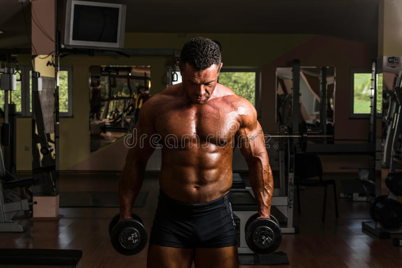 Body builder doing heavy weight exercise for biceps with dumbbell stock photo