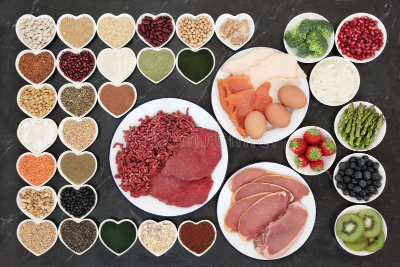 Body Building Health Food. With meat, fish, supplement powders, dairy, fruit, vegetables, pulses, nuts, seeds, grains and cereals on porcelain plates royalty free stock image