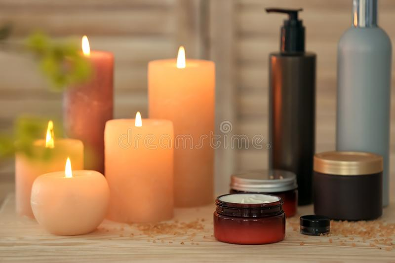Body care cosmetics and burning candles royalty free stock photography
