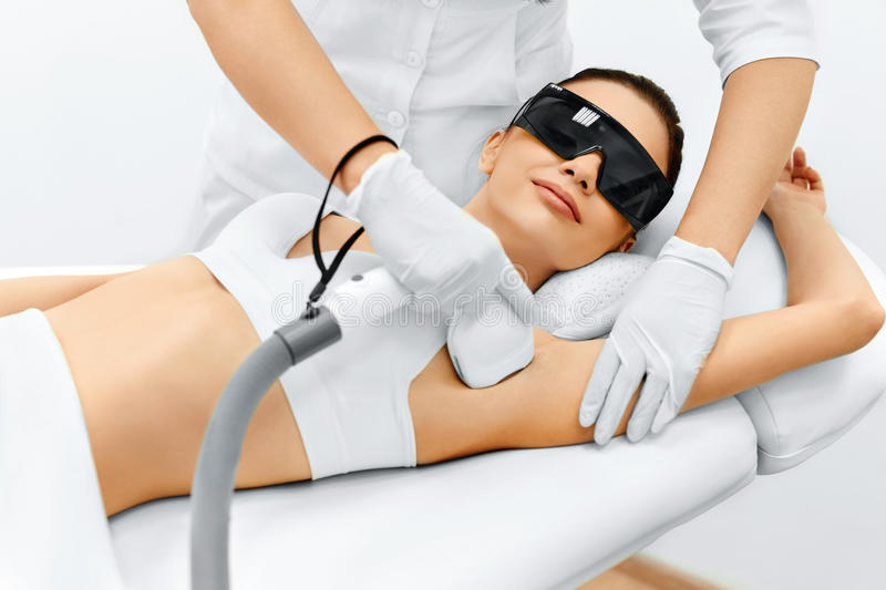 Body Care. Laser Hair Removal. Epilation Treatment. Smooth Skin. Body Care. Underarm Laser Hair Removal. Beautician Removing Hair Of Young Woman's Armpit. Laser stock photography