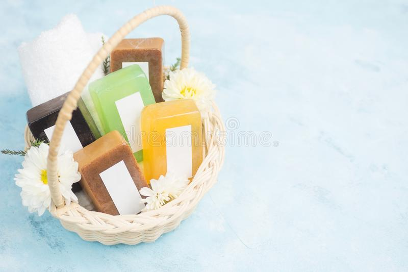 Body care mock up: Colorful soap bars with blank labels in wicker basket with flowers on blue background. Spa, massage royalty free stock photography