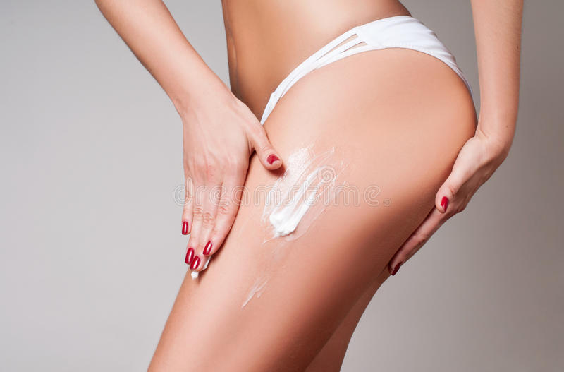 Body care. Woman applying cream on legs and buttocks from cellulite stock photos