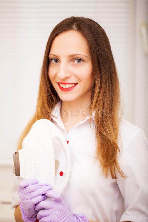 Body Care. Woman doctor displaying machine for laser hair removal stock image