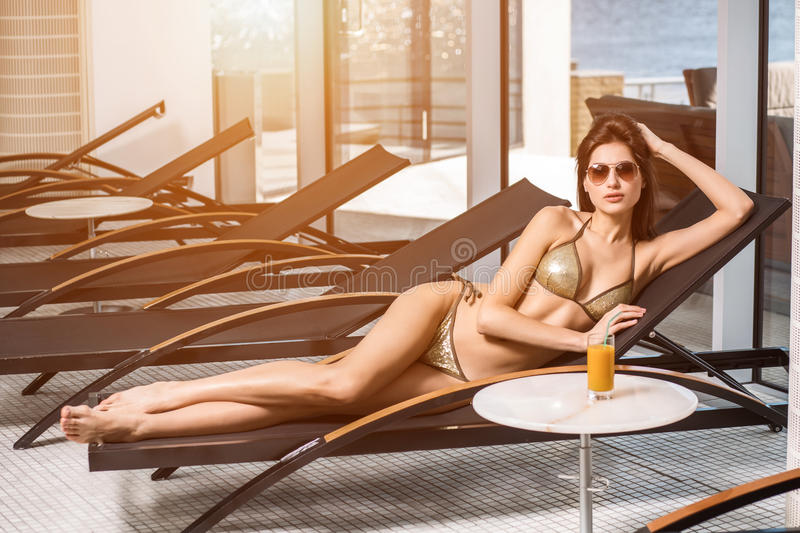 Body care. Woman with perfect body in bikini lying on the deckchair by swimming pool. At resort spa hotel royalty free stock image