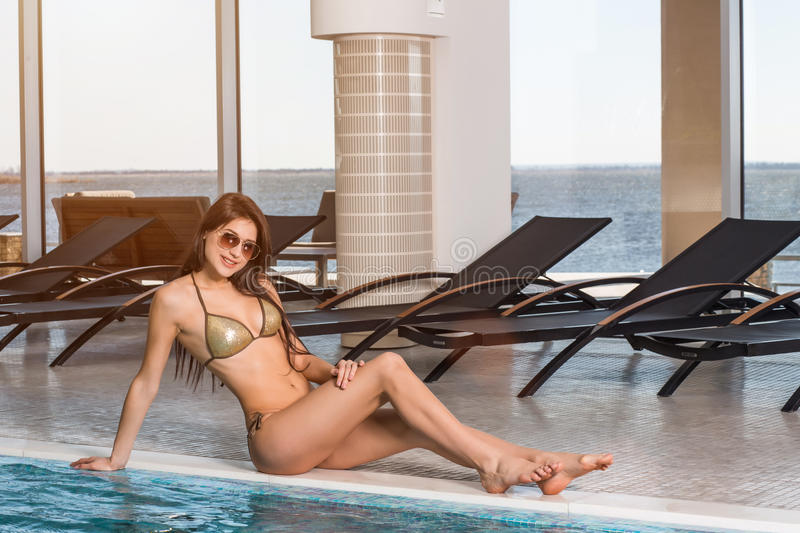 Body care. Woman with perfect body in bikini lying near the deckchair by swimming pool. At resort spa hotel stock photo