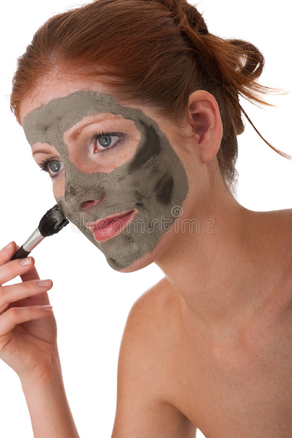 Body care - Young woman with mud mask stock images