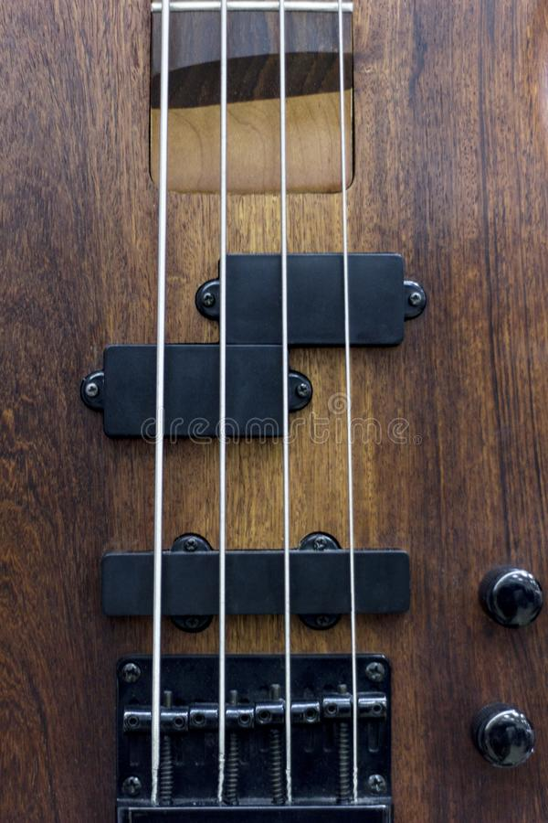 Body of a classic bass guitar. Electric bass guitar element. Guitar neck closeup. Chord. Selective focus. stock photos
