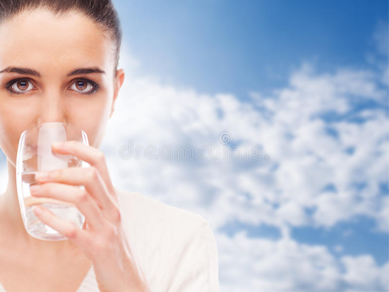 Body hydration. Young woman drinking a glass of fresh water, body hydration concept stock photography