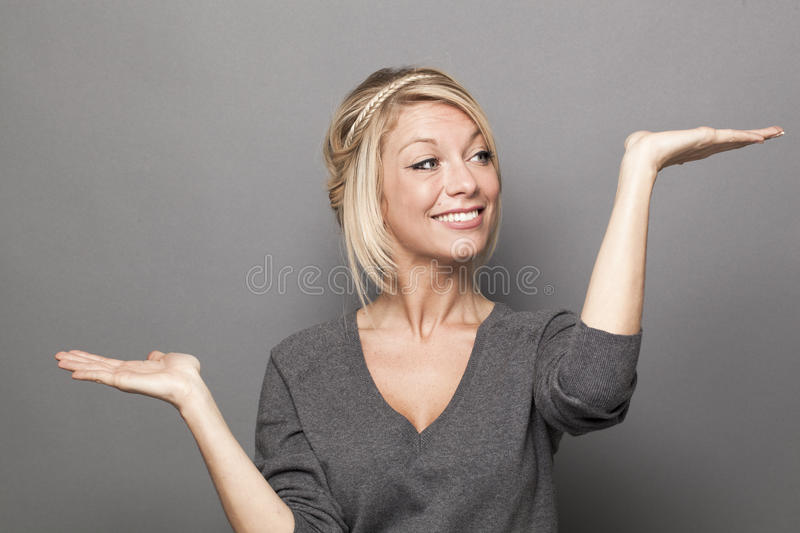 Body language concept for 20s blond woman. Body language concept - 20s blond woman weighting something on both palms of her hands for up and down value of royalty free stock photos
