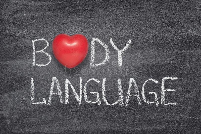Body language heart. Body language phrase written on chalkboard with red heart symbol instead of O stock image