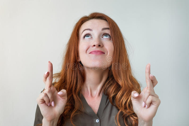 Body language. Superstitious caucasian woman with ginger hair and pretty face crossing fingers for good luck. stock photography