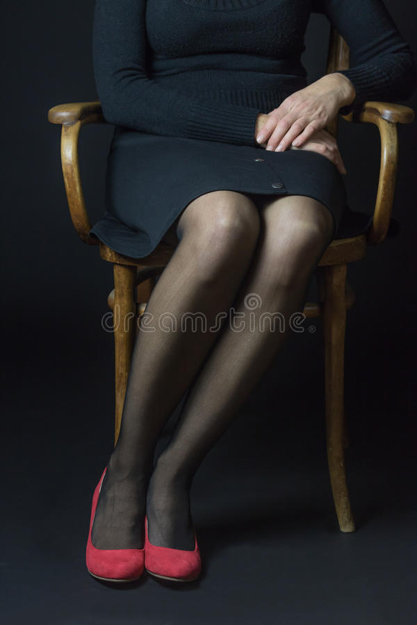 Body language - Woman is sitting with parallel legs. Woman in red pumps and black stockings is sitting with parallel legs on an old chair. This position reflects royalty free stock photo