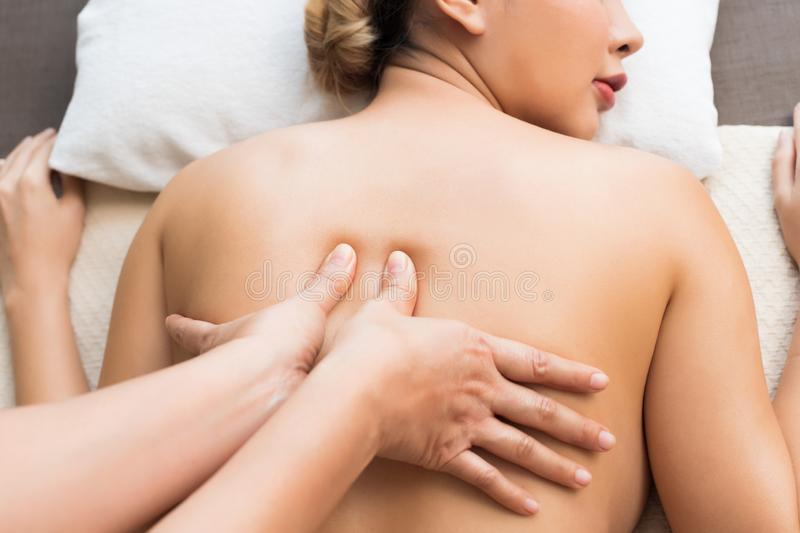 Therapist Spa body massage woman hands treatment. Body Massage on naked back of Mix Race Caucasian Asian women by pressing fingers on pain or stress muscle point royalty free stock photo
