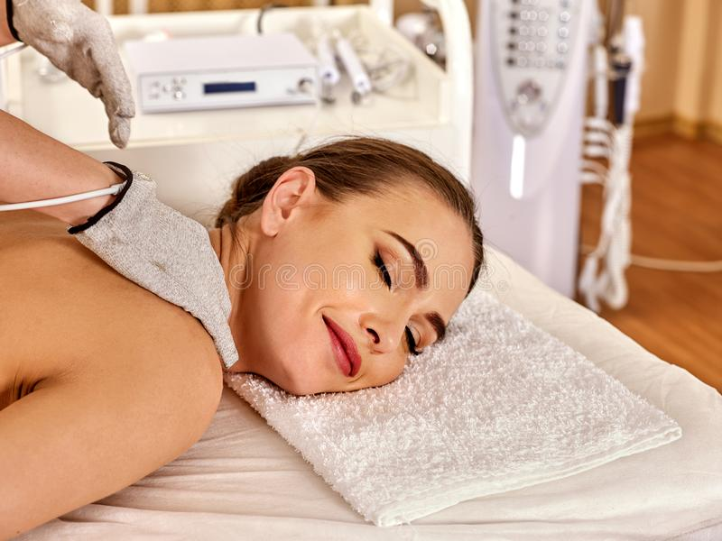 Body massage of silver threaded gloves at beauty salon. Electric stimulation skin care of woman. The best spa salon. Beautician wearing electricity glove stock photos
