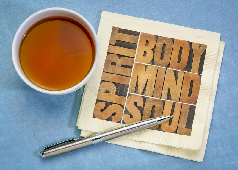 Body, mind, soul and spirit concept. Body, mind, soul and spirit - text in vintage wood letterpress printing blocks on a napkin with a cup of tea, health royalty free stock photography