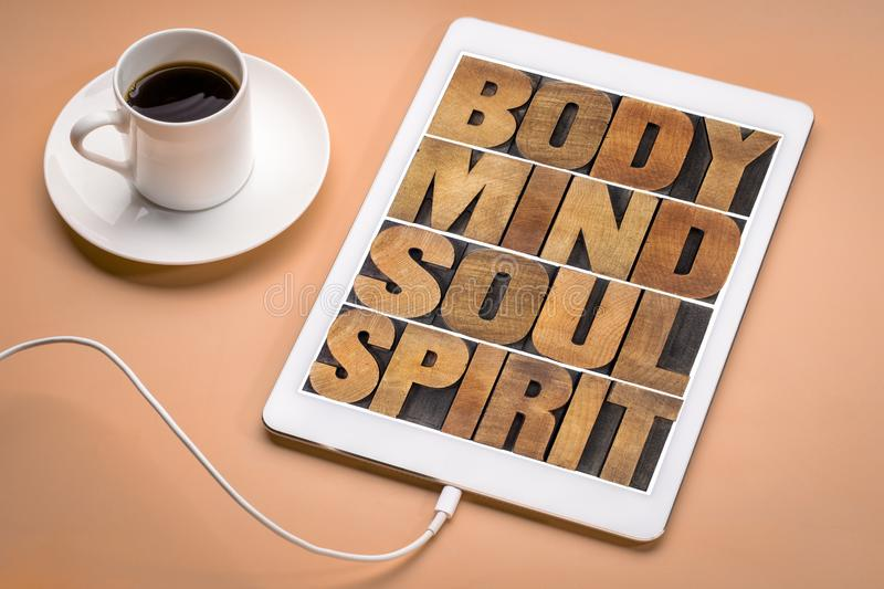 Body, mind, soul and spirit on tablet. Body, mind, soul and spirit - wellness concept - text t in letterpress wood type on a digital tablet with cup of coffee royalty free stock photography