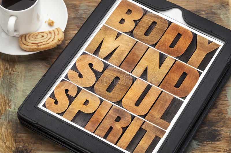 Body, mind, soul and spirit on tablet. Body, mind, soul and spirit - wellness concept - a word abstract in letterpress wood type on a digital tablet with cup of royalty free stock photo