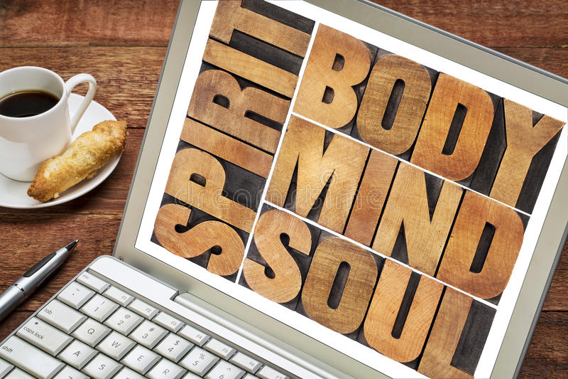 Body, mind, soul and spirit. Word abstract - a collage of isolated text in vintage wood letterpress printing blocks on a laptop screen with a cup of coffee royalty free stock image