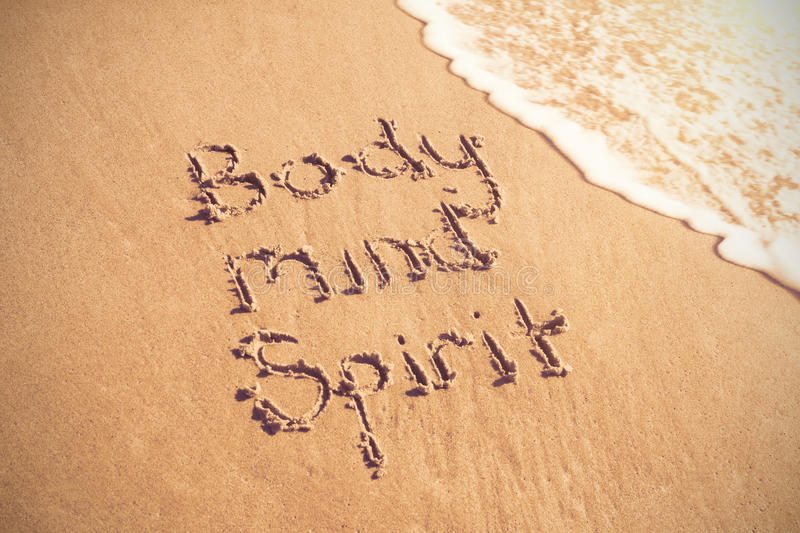 Body mind spirit text written on sand with surf stock photography