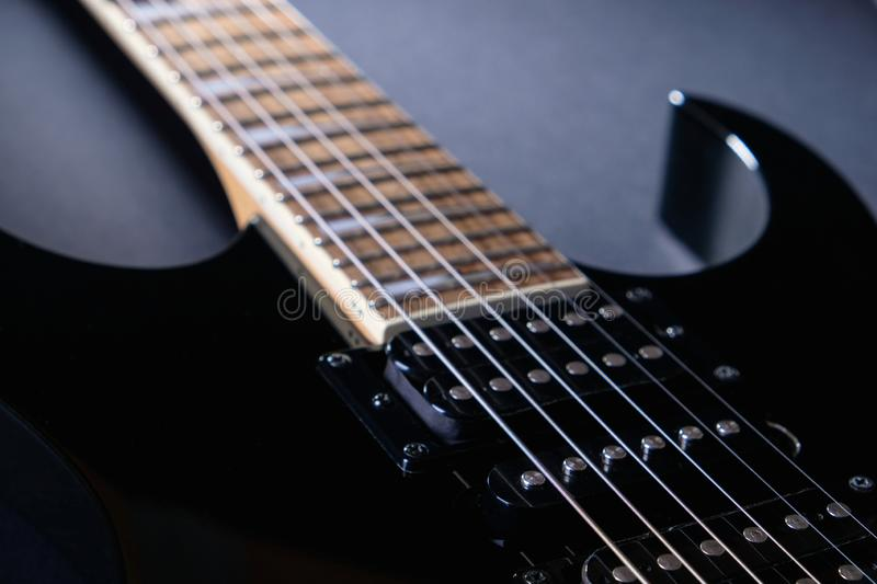 Body and neck of black electric guitar. Close up detail. On dark. Background stock image