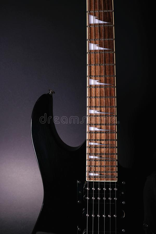 Body and neck of electric guitar. Close up detail. Accentuated shapes by illumination. With copy space. On dark backgrouna royalty free stock images
