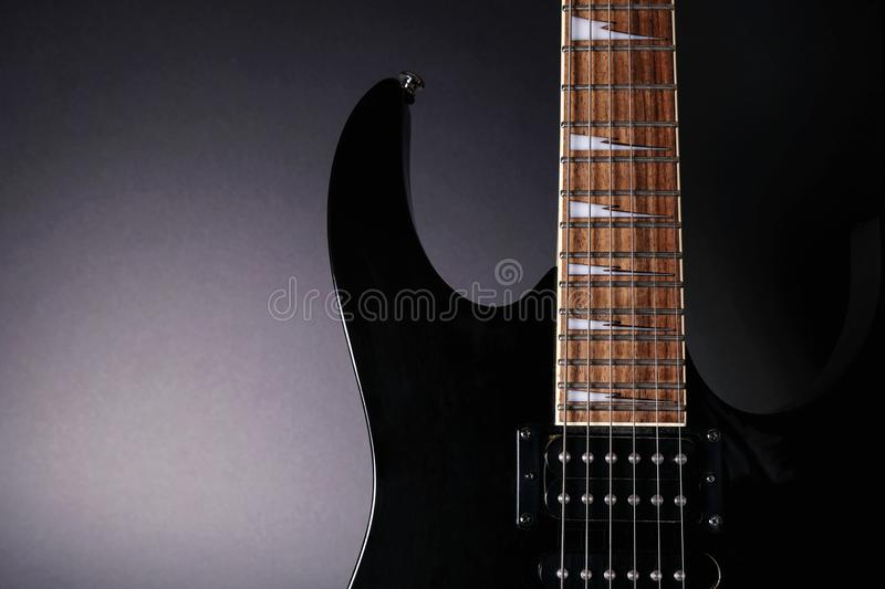 Body and neck of electric guitar. Close up detail. Accentuated shapes by illumination. With copy space on dark. Background stock photos