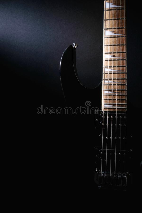 Body and neck of electric guitar. Close up detail. Accentuated shapes by illumination. With copy space on dark. Background stock images