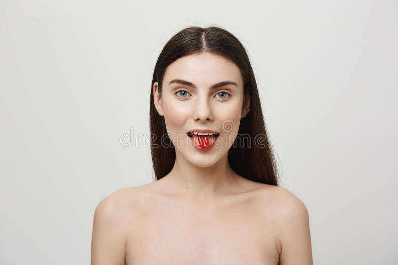 Body needs vitamins every day. Portrait of good-looking young caucasian woman sticking out tongue and holding two pills stock photo